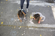 Sisters drawing with sidewalk chalk - HEROF09564