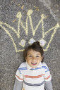 Portrait of boy with sidewalk chalk crown overhead - HEROF09570
