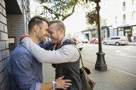 Smiling homosexual couple hugging on urban sidewalk - HEROF09576