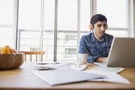 Man in headphones using laptop at table - HEROF09582