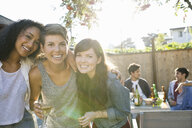 Portrait of smiling friends drinking at backyard barbecue - HEROF09594