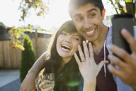 Enthusiastic couple taking selfie of engagement ring - HEROF09597