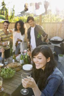 Smiling woman drinking wine at backyard barbecue - HEROF09600