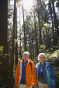 Portrait of smiling senior couple in sunny woods - HEROF09633