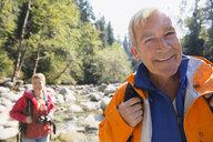 Portrait of smiling senior man hiking in woods - HEROF09639