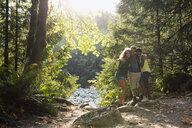 Portrait of friends hugging in sunny woods - HEROF09648