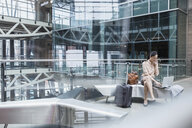 Businesswoman using laptop and cell phone in airport - HEROF09693