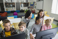 Teacher watching elementary students use computers in classroom - HEROF09732