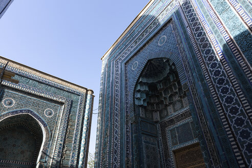 Low angle view of tall arches of an Islamic Madrasa building with blue and white patterned glazed tiles. - MINF10132