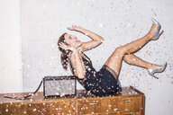 Laughing young woman under shower of confetti at a party - PNEF01202