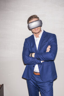 Young man wearing blue suit using Virtual Reality Glasses - PNEF01208