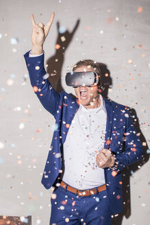 Screaming young man man with Virtual Reality Glasses standing in between confetti shower at a party - PNEF01211