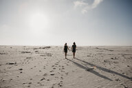 South Africa, Western Cape, Noordhoek Beach, back view of two young women strolling on the beach - LHPF00401
