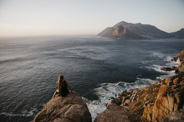 South Africa, Western Cape, woman sitting on a rock looking at view, seen from Chapman's Peak Drive - LHPF00410