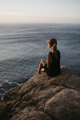 South Africa, Western Cape, woman sitting on a rock looking at view - LHPF00413