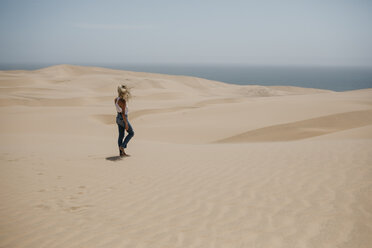 Namibia, Walvis Bay, Namib-Naukluft National Park, Sandwich Harbour, woman walking in dune landscape - LHPF00434