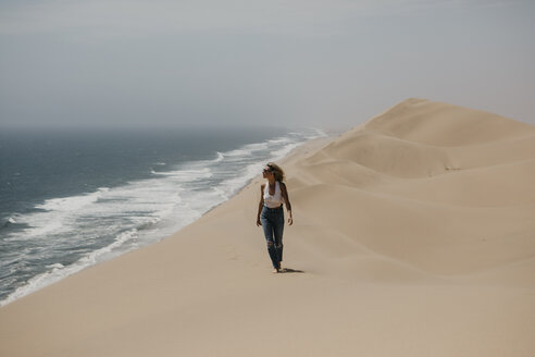 Namibia, Walvis Bay, Namib-Naukluft National Park, Sandwich Harbour, woman walking in dune landscape at the sea - LHPF00437