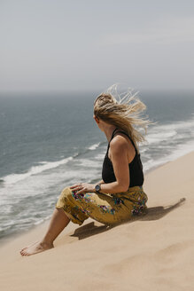 Namibia, Walvis Bay, Namib-Naukluft National Park, Sandwich Harbour, woman sitting in dune landscape at the sea - LHPF00440