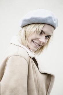 Porträt einer lächelnden jungen Frau mit Baskenmütze, Deutschland - JESF00218
