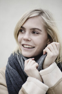 Portrait of smiling blond young woman wearing scarf - JESF00221