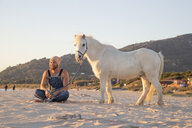 Spain, Tarifa, happy man with pony sitting on the beach - KBF00478
