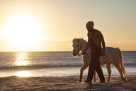 Spain, Tarifa, man walking with pony on the beach at sunset - KBF00481