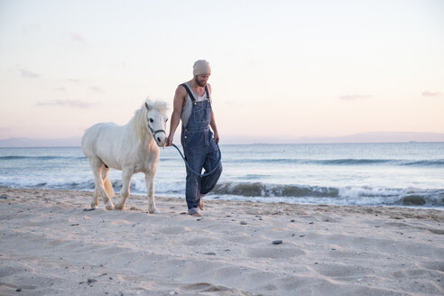 Spain, Tarifa, man walking with pony on the beach - KBF00487