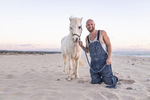 Spain, Tarifa, portait of smiling man with pony on the beach - KBF00490