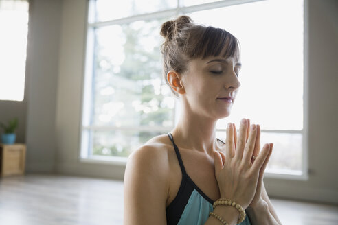 Woman meditating with hands in prayer position - HEROF09796
