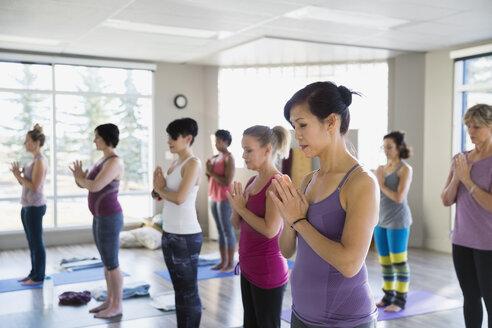 Women with hands at heart center yoga class - HEROF09829