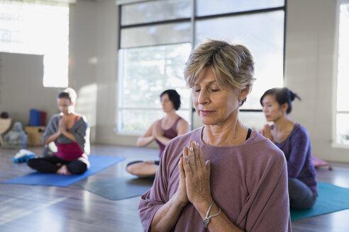 Serene women meditating in yoga class - HEROF09856