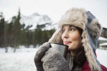 Woman in fur hat drinking hot cocoa outdoors - HEROF09904