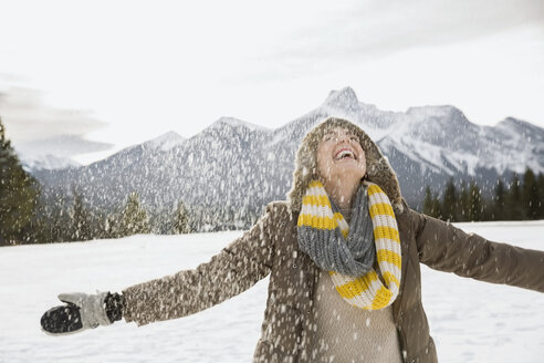 Snow falling around exuberant woman with arms outstretched - HEROF09910