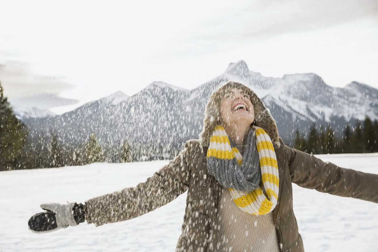 Snow falling around exuberant woman with arms outstretched - HEROF09910 - Hero Images/Westend61
