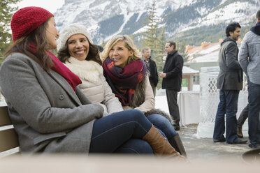 Women in warm clothing sitting on patio bench - HEROF09913