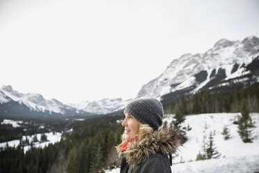 Woman in warm clothing below snowy mountains - HEROF09916
