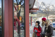 Women in warm clothing window shopping at storefront - HEROF09949
