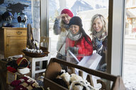 Women in warm clothing window shopping at storefront - HEROF09961