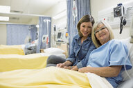 Portrait of smiling daughter visiting mother in hospital - HEROF10039
