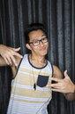 Portrait of cool man in tank top gesturing - HEROF10096