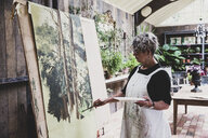 Senior woman wearing glasses, black top and white apron standing in studio, working on painting of trees in forest. - MINF10215