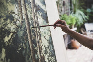 Close up of artist working on painting of trees in forest. - MINF10218