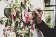 Close up of artist working on painting of pink tea roses, leaves, berries and other flowers. - MINF10263