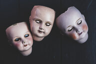 Close up of three porcelain dolls' heads on black background. - MINF10269