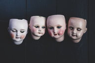 Close up of four porcelain dolls' heads on black background. - MINF10272