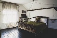 Interior view of attic bedroom with dark wooden floor and white walls, antique French double bed with green throw and lace net curtain in window. - MINF10275