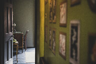 View along corridor with vintage pictures on green wall, open brown wooden door to study with antique desk and chair. - MINF10278