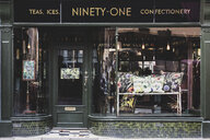 Exterior view of interior design store with floral print cushions on vintage metal bench in shop window. - MINF10284
