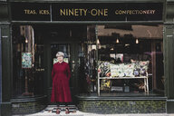 Smiling senior woman wearing glasses and red dress standing front of interior design store, looking at camera. - MINF10287
