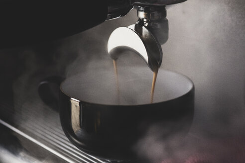Close up of black mug on espresso machine, hot coffee pouring from spout. - MINF10323